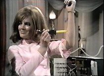 Angie (Geraldine Moffatt) demonstrates the Bag's 'foolproof' surgical knife on herself.